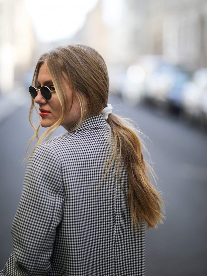 Portrait of a woman with low ponytail and sunglasses