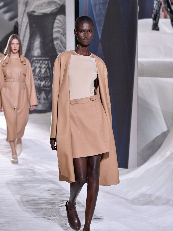 Black model in beige outfit with long coat