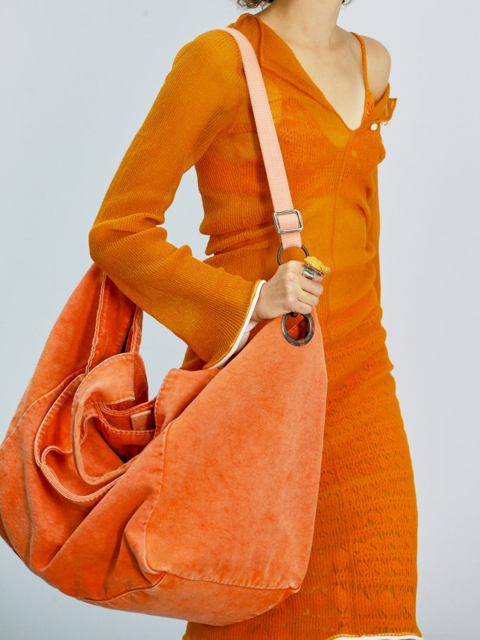 Details of a runway look in orange with an XXL pocket