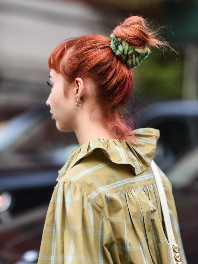Woman with red hair and a high bun from behind