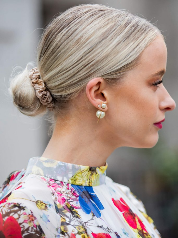 Woman with a topknot and pearl earrings from the side