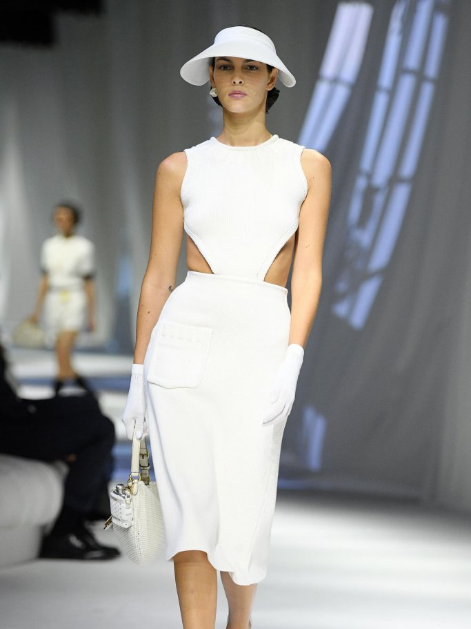 Model in a white dress with cut-outs and an elegant hat