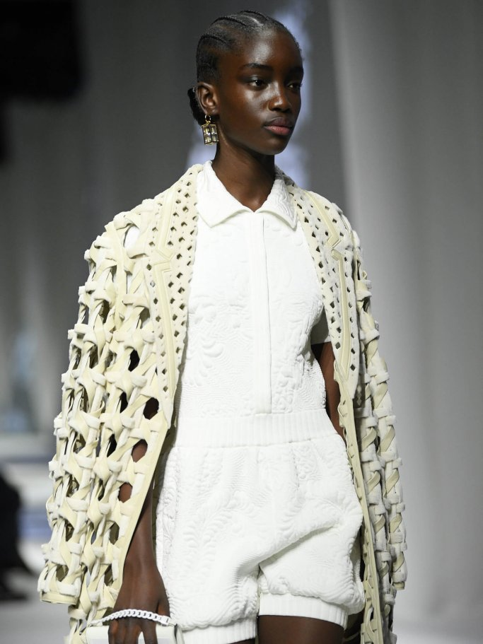Black model in white outfit and coat with cut-outs