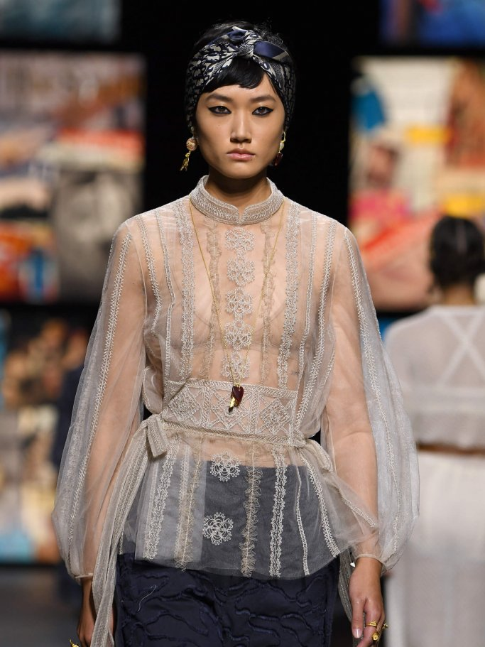 Model with a transparent blouse and hair scarf